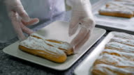 Baker by hands neatly folded freshly baked eclairs with sugar powder on a beautiful white plates in the kitchen at the bakery. Many delicious cakes on the table video