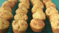 Baker hand takes one mini Muffins cake out off cooling rack. video