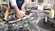 Baker hands kneading dough in flour on table video