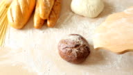 Baker is putting freshly baked loaf of homemade organic sourdough rye bread video