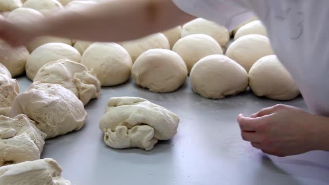 Baker kneading dough in a bakery video