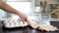 Baker taking eggs from carton and putting on kitchen table. Fresh chicken eggs video