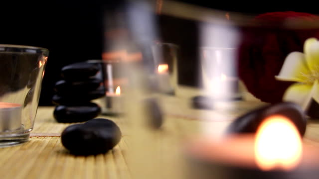 Balanced black spa therapy stones surrounded by candles video