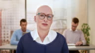 Bald female designer making a video call from the office video