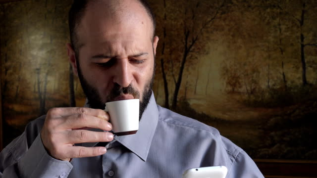 bald man takes coffee while checking email on mobile video