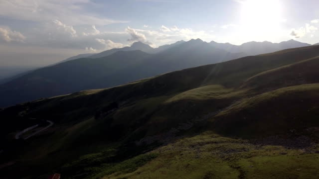 bald mountain in summer sunny sunset or sunrise dawn or dusk with road and lodge 4k aerial drone forward flight wide nature establishing shot video