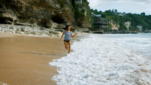 Bali Island beach. Brunette smile runs across the sand on the beach and cool your feet in the water. Woman enjoying the sun, blue ocean. Against the backdrop of stunning views video