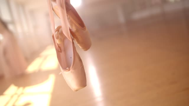 Ballet shoes hanging on a barre in a ballet studio video