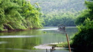 Bamboo raft in River Kwai with tree and mountain and blue sky video