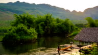 Bamboo raft in river with tree and mountain and blue sky from day to night video