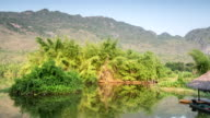 Bamboo raft in river with tree and mountain and blue sky video