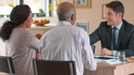 Banker shaking hands with multi ethnic senior couple at home video