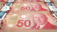 Banknotes of fifty canadian dollars of the bank of Canada rolling on screen, coins of the world, cash money, loop video