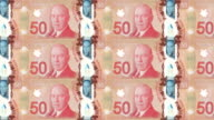 Banknotes of fifty canadian dollars rolling on screen, cash money, loop video