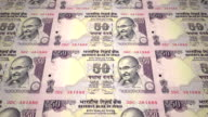 Banknotes of fifty indian rupees of the bank of the Republic of India rolling on screen, coins of the world, cash money, loop video