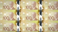 Banknotes of one hundred canadian dollars of the bank of Canada rolling on screen, coins of the world, cash money, loop video