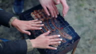 Barbecue browned sausages on the hot grill, warm hands closeup video