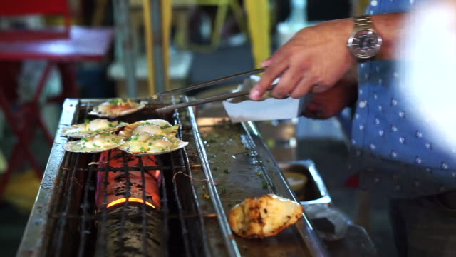 Barbecue grill seafood, grilling scallops with butter on charcoal fire video