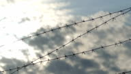 Barbed wire against the blue sky clouds video prison video