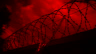 Barbed wire at the top of fence against the gloomy, dark, blood red sky with clouds. Shot in motion video