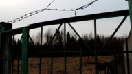 barbed wire fence gate prison exterior on heaven background video