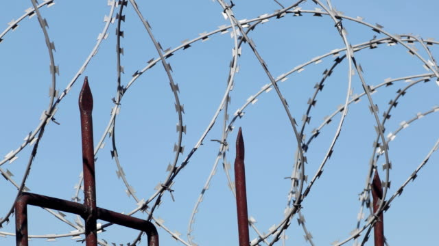 Barbed wire on metal fence with pointed rods. Sliding along. Close. video