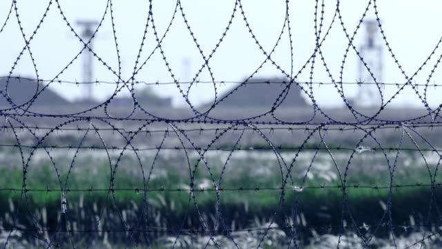 Barbed wire. Selective focus of barbed wire at airport with radar antennas in the background. video