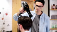 Barber combing the hair of the client before haircut at a barber shop video