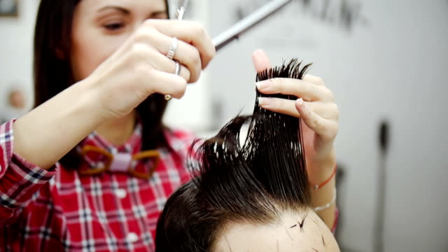 Barber cuts the hair of the client with scissors. Slow motion video