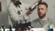 Barber drying hair with hair blower video