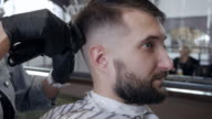 Barber hands cutting hair with electric razor at a barber shop video