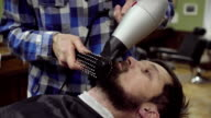 Barber is drying beard a bearded man with hairdryer in a barber shop video