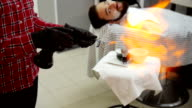 Barber razor ignites the flame of fire. Slow motion video