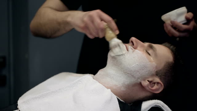Barber shaves the beard of the client in the barbershop video
