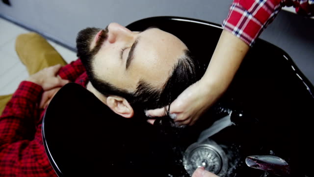 Barber Washing Male Hair in a Barbershop. Slow motion video