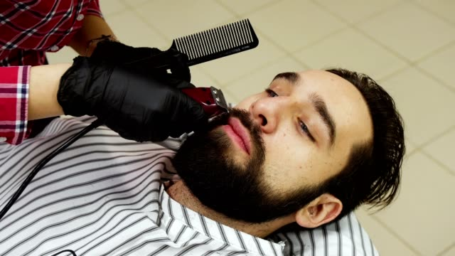 Barber woman trimming beard of client with clipper at barbershop video