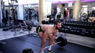 Bare chested man deadlifting barbells in a gym video