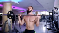Bare chested man weightlifting barbells in a gym video