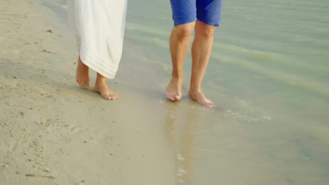 Bare feet of a man and a woman walk along the sand along the sea. Holiday together in the tropics. Steadicam shot video