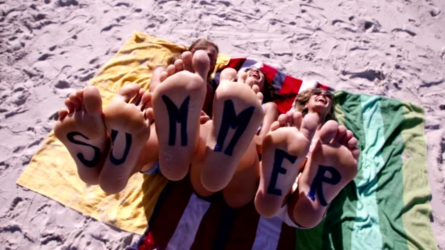 Bare feet of female friends with word summer video