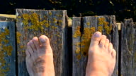 Bare feet on wooden boards with moving toes video