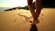 Barefeet walking inside heart shape drawn on sand video