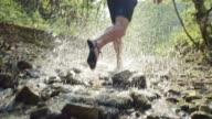 SLO MO Barefoot runner running across a creek in sunshine video