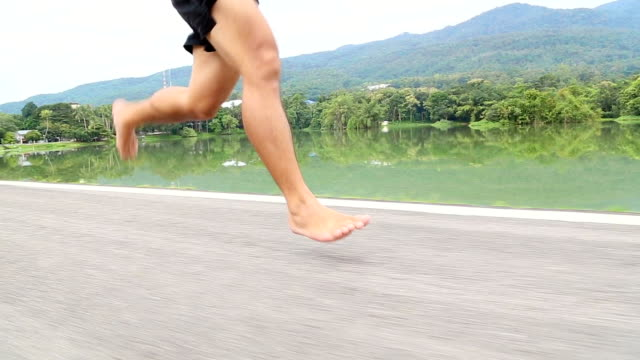 Barefoot running on road in the park with mountain background video