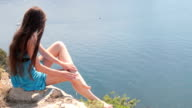 barefoot young woman resting  by the sea video