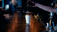Barista adding syrup to a milk shake video