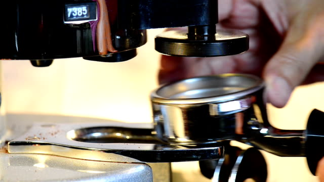 Barista dispensing ground coffee from grinder to portafilter. video