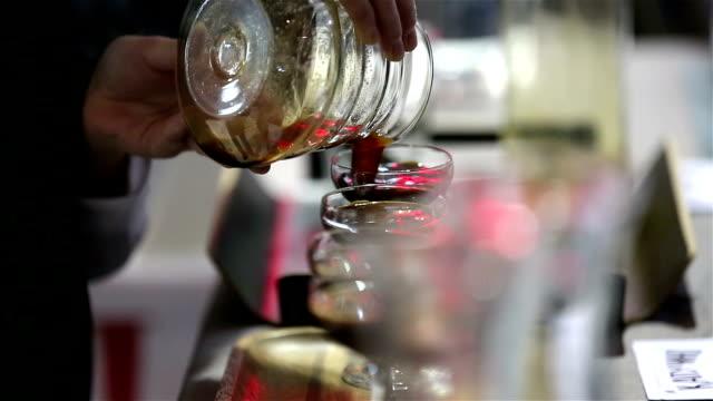 Barista pours coffee beverage glasses. video