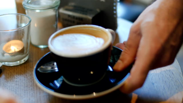 Barista serving coffee to customers in coffee shop video