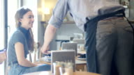Barista serving coffee to male and female friends video